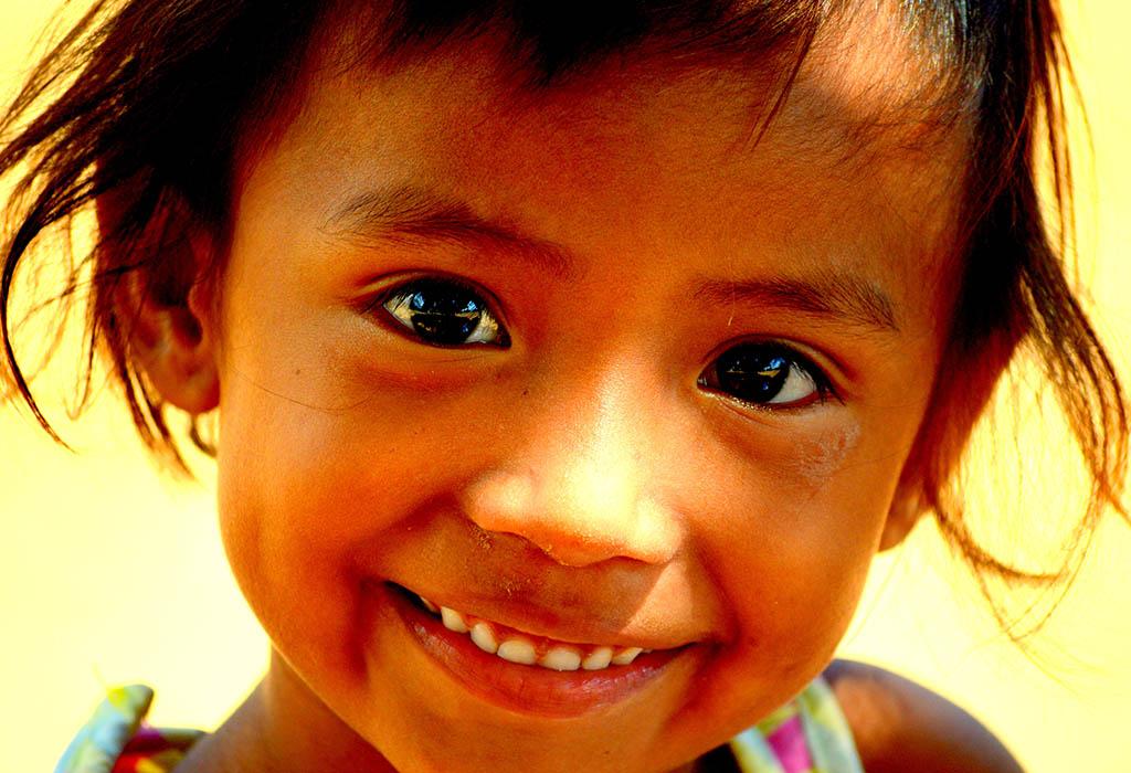Ein ca. 4-jähriges Kind mit strubbeligen braunen Haaren schaut mit strahlenden Augen in die Kamera.